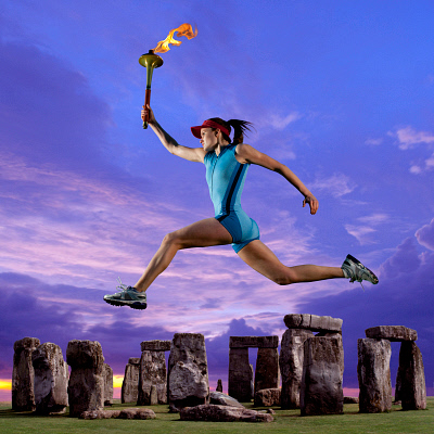 Athlete running with Olympic torch near Stonehenge BLD0108181