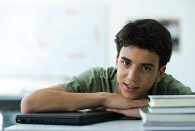 Male high school student sitting at desk PHA0071380