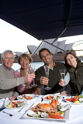 couples toasting drinks on yacht STB0116628