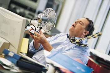 Businessman in a Hot Office Holding an Electric Fan to Himself DVP0026012