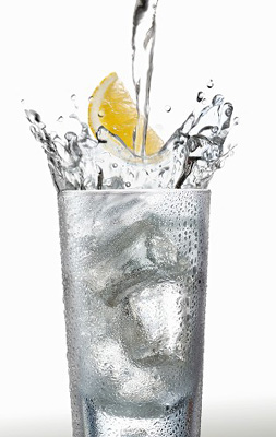 Pouring water into a glass with a wedge of lemon FCL0037028