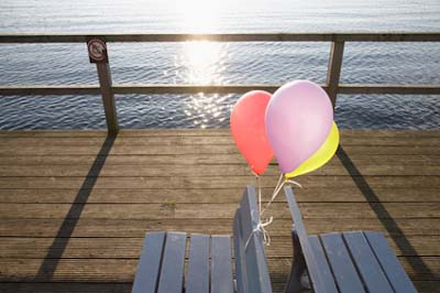 three colourful balloons tied on benches on pier BDG0017598