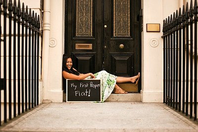 Young woman sitting at front door of her new home CRB0172992