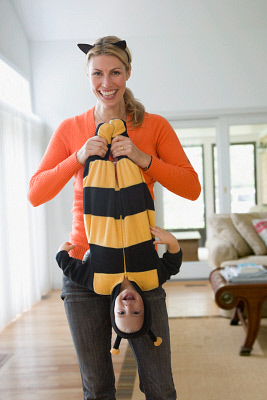 Caucasian mother playing with baby daughter in bee costume. BLD0101805