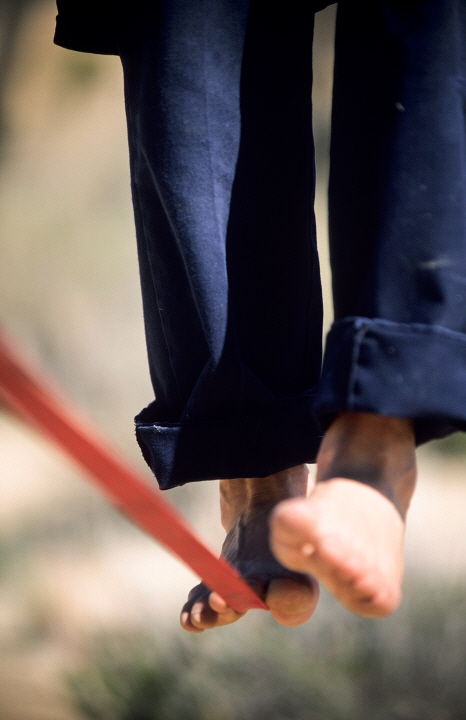 Close up of a man's bare feet balancing on a tight rope or slackline in the California desert AUR0005090