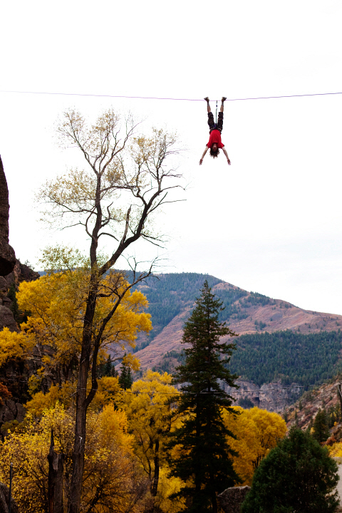 A young man does a bat hang from a slack line after walking the line AUR0012270