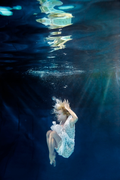 Caucasian woman in dress swimming under water BLD0112330