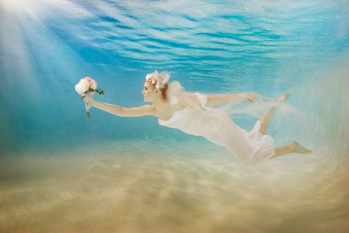 Caucasian bride in wedding dress swimming under water BLD0112367