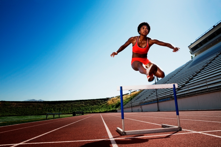 Athletic woman jumping over hurdle BXP0048686