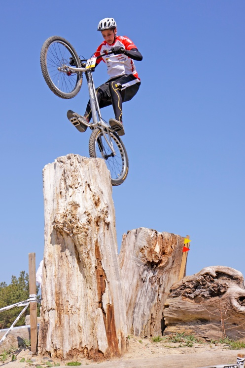 Teenager jumping over a tree stump with his bike at a biking trial. IMR0231079