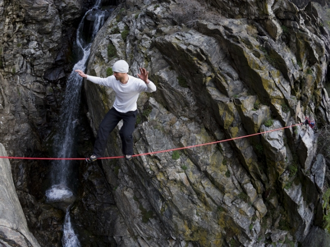 Man walking across rope with rock and waterfall in background RBI0020350