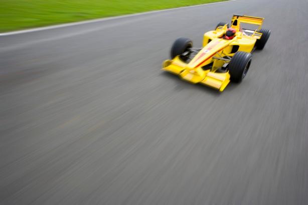Formula One Racecar Speeding Down Racetrack BRD0059286