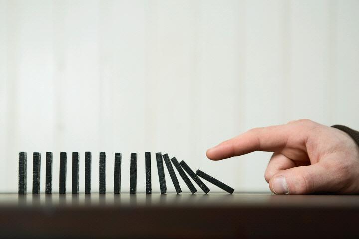 Man pushing dominoes over  FAN0002443