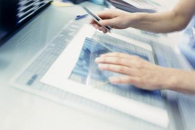 Woman working on a blueprint. ©Media Bakery #FLT0051550