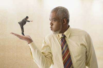 Giant businessman blowing on miniature businessman. ©MediaBakery #BLD0066995