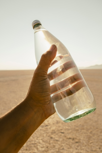 The landscape of the Black Rock Desert in Nevada. An essential element for survival. A man's hand holding a bottle of water. Filtered mineral water.