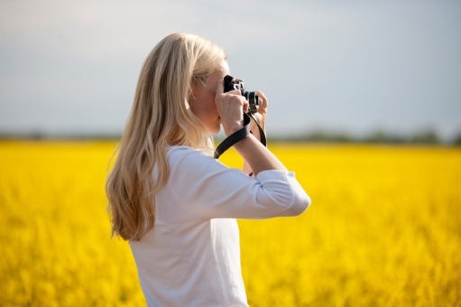 Media Bakery ID: LUV0017976 A young woman taking a photograph of a rape seed field in flower