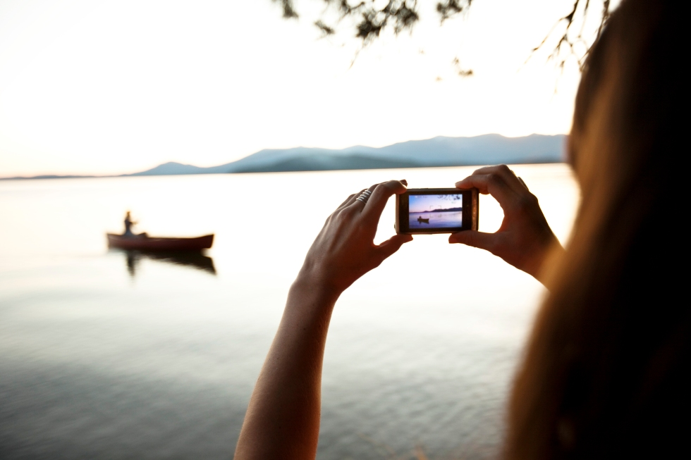 Media Bakery ID: AUR0015437 A woman takes a photo of a man canoeing on a lake at sunset in Idaho.