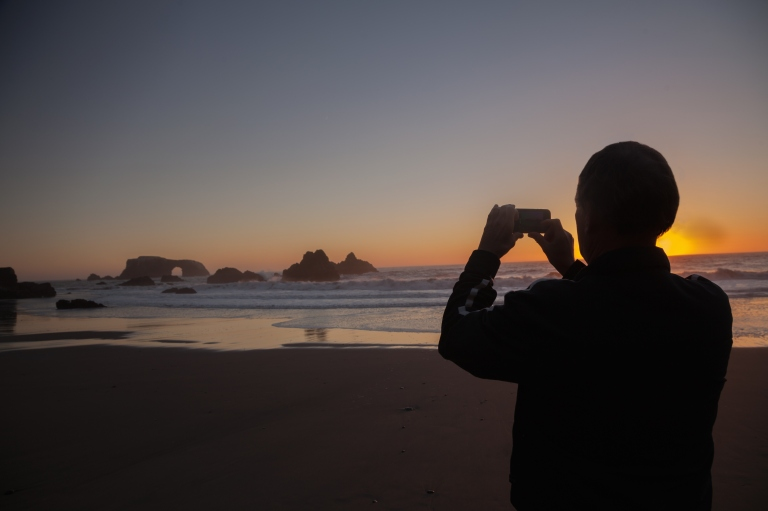 Media Bakery ID: PCH0112790 A man photographing sunset on a beach