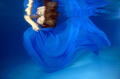 ImageID: ibxaaa02008289.jpg Woman presenting underwater fashion in pool