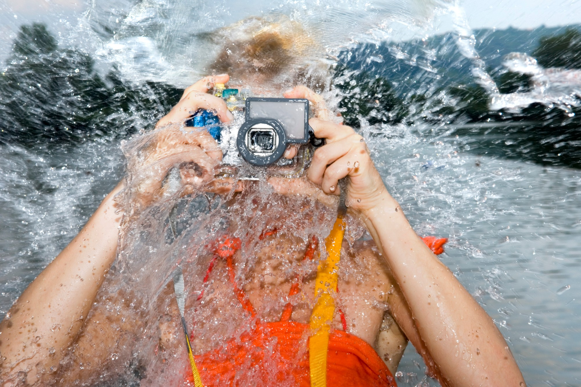 Image ID: PDI0257290 Woman splashed with water as she photographs with underwater camera