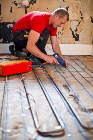 Media Bakery ID: MSK0000745 Man gluing floor heating with glue gun