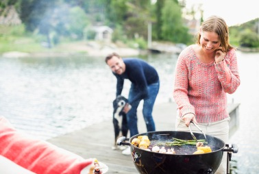 Media Bakery ID: MSK0007113Happy woman using mobile phone while barbecuing with man and dog in background on pier