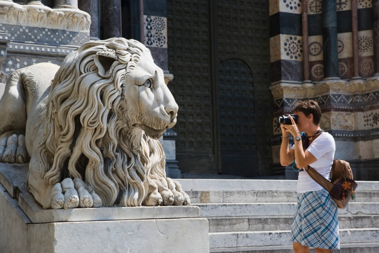 Media Bakery ID: PDI0296045 Italy, Liguria, Genoa, woman taking picture of lion statue at Cathedral of San Lorenzo