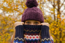 Media Bakery ID: CUL0132251 Close up portrait of young woman in park with jumper hiding face