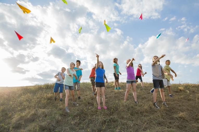 Media Bakery ID: HER0006670 Schoolchildren throwing paper aeroplanes on field