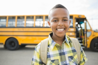 Media Bakery ID: HER0008914 Portrait of happy little boy against school bus