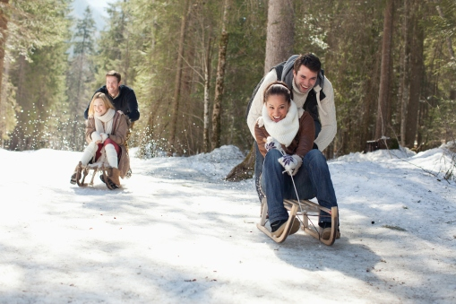 Media Bakery ID: OJO0044293 Smiling couples sledding in snowy woods