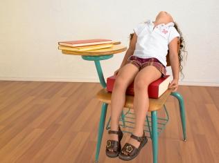 Media Bakery ID: SOM0003133 Girl Sitting on Large Book in School Desk