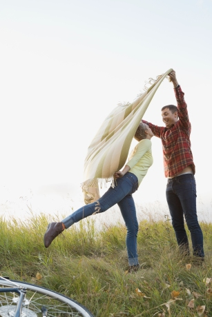 Media Bakery ID: HER0005742 Playful couple spreading out blanket at field