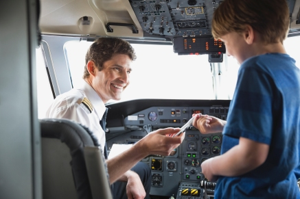 Media Bakery ID: HER0005950 Male pilot giving toy plane to boy in airplane cockpit