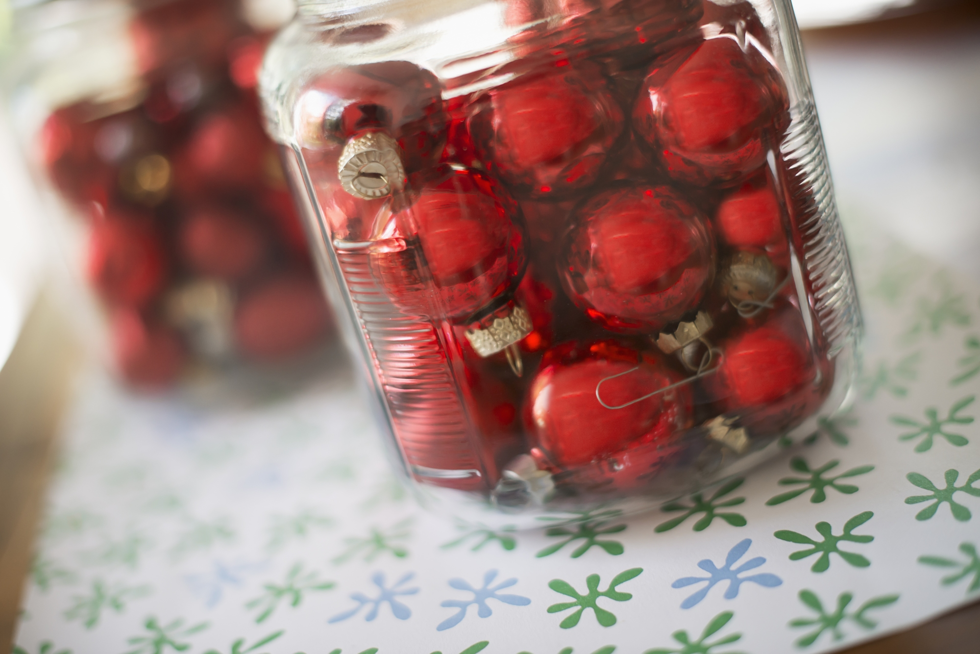 Media Bakery ID: MNT0008264 Red glass ball Christmas ornaments in glass jars on a tabletop.
