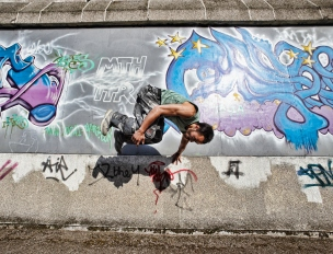 Media Bakery ID: DVP0152091 Young Man doing parkour flip against graffiti wall