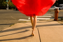 Media Bakery ID: IMS0248661 Waist down shot of young woman strolling along sidewalk wearing flowing red skirt