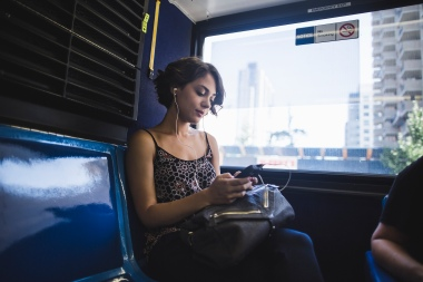 Media Bakery ID: IMS0249085 Young woman commuting on bus listening to music on smartphone, New York, US