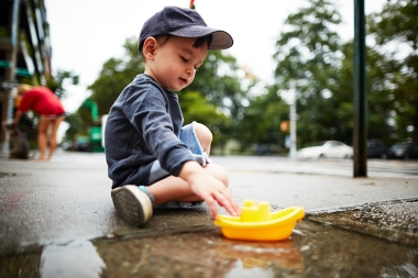 Boy playing with toy boat on water on pavement