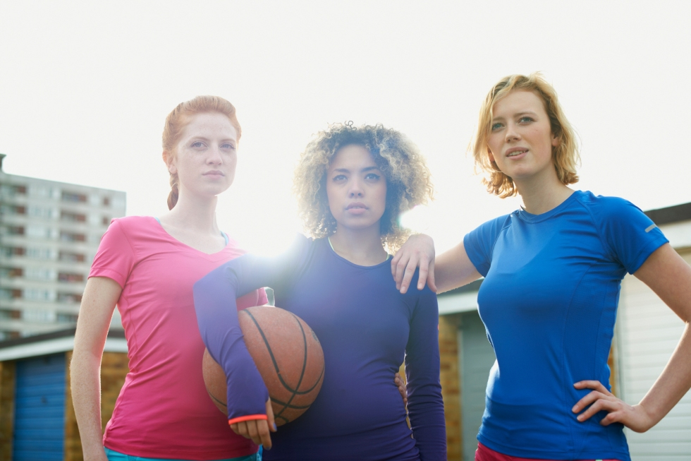 Portrait of three women exercising together holding a basketball