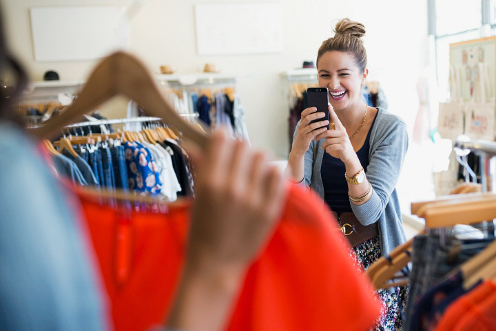 Woman photographing friend holding shirt in clothing shop
