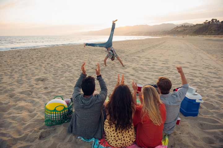 Group of friends sitting on beach watching friend do cartwheels on and sunset rear view
