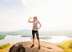 Young woman standing on top of mountain and flexing muscles
