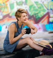 Stylish teenage girl sitting on sidewalk with camera in front of graffiti wall