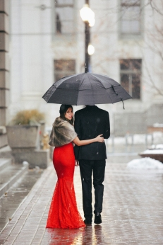 A woman in a long red evening dress with fishtail skirt and a fur stole and a man in a suit walking through snow in the city
