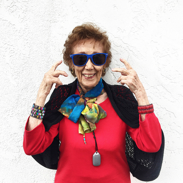 Older woman wearing sunglasses and flashing gang sign