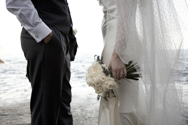 Bride and groom standing by sea