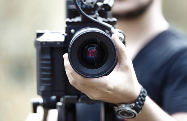 Hand of cameraman focusing and using video camera