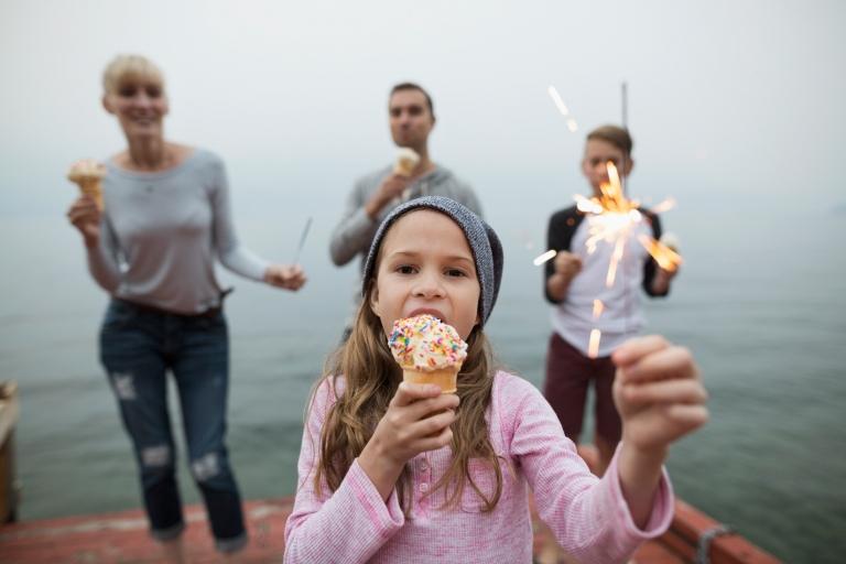 Smiling family ice cream and sparkler fireworks lake